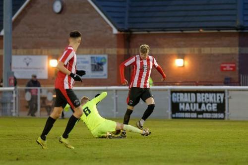 Photo 16 Ben Cook makes a sliding tackle